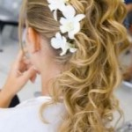 Wavy bride updo with small white flowers.