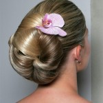 Elegant updo perfect for a bride with a fresh pink orchid.
