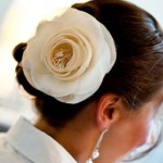 Huge ivory flower in elegant updo for brides.