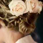 Wavy updo with soft orange pink roses.