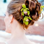 Bright green orchids in bridal updo.