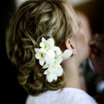 Elegant wavy updo with small white flowers.