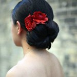 Beautiful red flowers stand out in elegant bride updo.