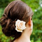 Low wavy updo with a single rose.