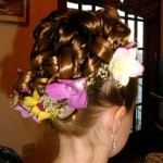 Curly updo with purple, yellow and white flowers.