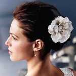 Wedding hairstyle chignon with big white flower.