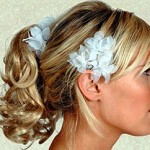 Blonde curly wedding hairstyle with flowers.