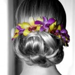 Wedding hairstyle with yellow and purple orchids.