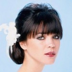 Wedding hairstyle with bangs and flowers.