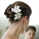 Simple and cahrming wedding updo with two white flowers.