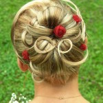 Blonde wedding updo decorated with small red roses.