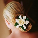 Gardenia flower with leaves on a classic wedding bun hairstyle.
