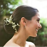 Low bun hairstyle for wedding with baby's breath flowers.