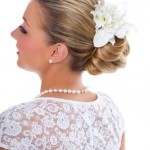 Young bride wearing pearls and lace top with wedding updo hairstyle with white flowers.