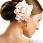 Sleek wedding hairstyle with ivory rose.