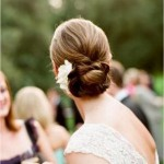 Low bun hairstyle with white flower.