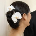 Fresh white orchids in elegant wedding hairstyle.