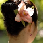High wedding updo with gorgeous pink orchid.