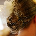 Bun hairstyle with flower and lace netting.