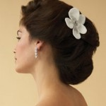 Grand wedding updo with single white flower.