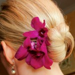 Blonde wedding bun with dark pink orchids.