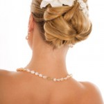 Wedding updo with blonde hair and white flowers.