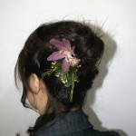 Brunette hair wedding upstyle with purple flower.