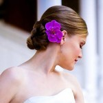 Low bun with bright purple flower.