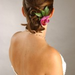 Gorgeous wedding updo with pink flower and leaves.