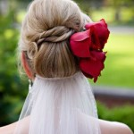 Bride updo with red roses and veil.