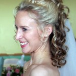 Half up half down bride hairstyle with curls, flowers and veil.