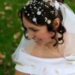 Bridal hairstyle with lots of small flowers and white veil.