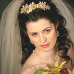 Curly bride hairtyle with a crown of flowers and an ivory veil.