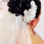 Curly updo for brides with veil and flower.