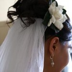 Curly updo for wedding with flower and veil.