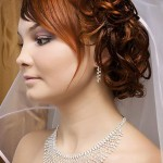 Bride updo with curls and white veil.