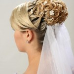 Bridal wedding veil coming out of elaborate, fancy bride updo.