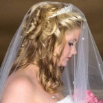 Wonderful half up half down wedding hairstyle with curls, tiara and a sheer veil covering the entire hairstyle.