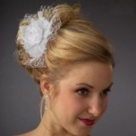 High wedding updo with white flower and white lace netting.