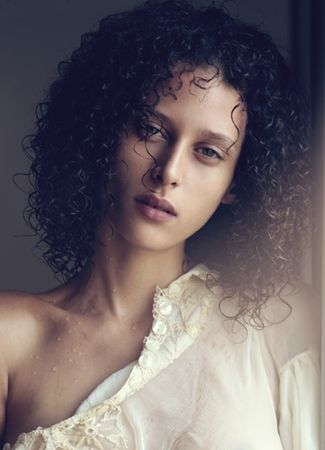 Ludmilla Dom Perignon shoulder length curly hair
