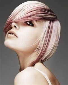 Short asymmetrical haircut in icy white blonde with dark red streaks