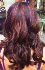 Warm honey blonde highlights through dark red hair.